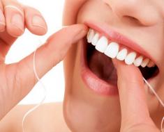Dùng chỉ nha khoa làm sạch răng