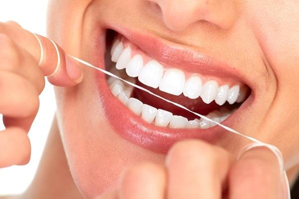 Dùng chỉ nha khoa làm sạch kẽ răng, bảo vệ răng sứ